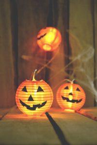 Jack O'lanterns Hanging out While People enjoy their Halloween